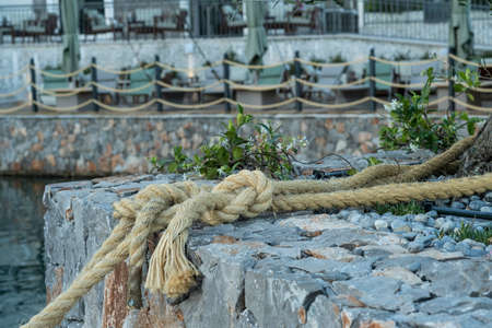 Close-up of a ship's rope as part of the decoration that adorns the embankment of a coastal town. In the background is a cafe on the seashore, tables are in the open air