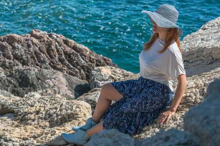Young woman tourist in a hat, sunglasses, blue skirt and white blouse is sitting on the rocks on the seashore near the water