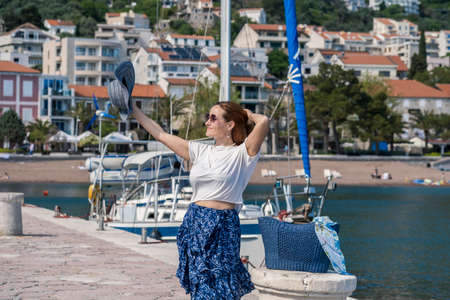 Young woman tourist in a hat, sunglasses, blue skirt and white blouse walking on the promenade of a seaside town. Residential buildings and a yacht moored at the pier are visible behind her