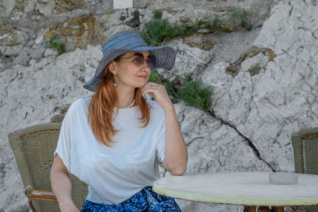 Young woman tourist in a hat, sunglasses, blue skirt and white blouse with long red hair is sitting on a outdoor cafe. Rock is seen behind her Stok Fotoğraf