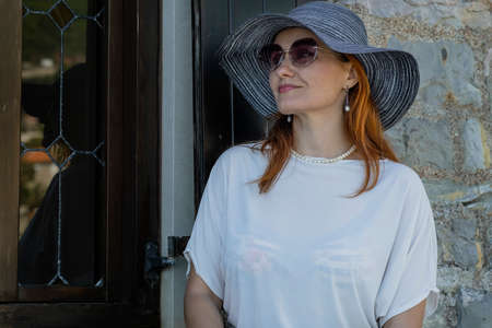 Portrai of a smiling woman tourist in a blue hat, sunglasses and white blouse with long red hair. Cafe entrance is behind her
