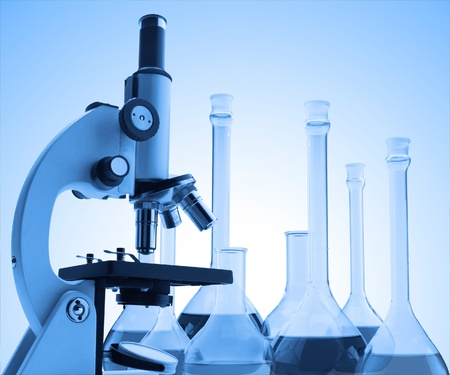 pharmacy equipment: Laboratory metal microscope and test tubes with liquid toning in blue color Stock Photo