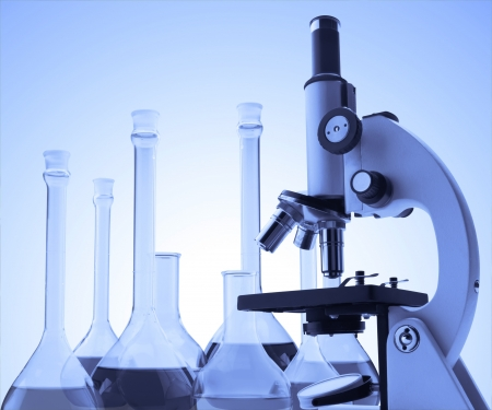 research study: Laboratory metal microscope and test tubes with liquid toning in blue color Stock Photo