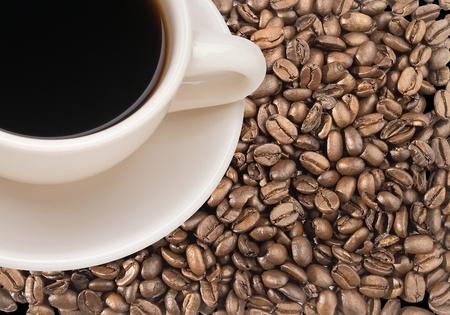cafe colombiano: Café recién hecho en la taza blanca sobre negro los granos de café tostado