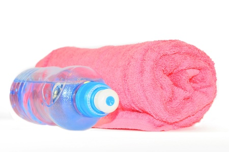 Twisted pink towel and bottle of sparkling water isolated on white