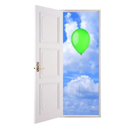 Open door in blue sky and green hot air balloon photo