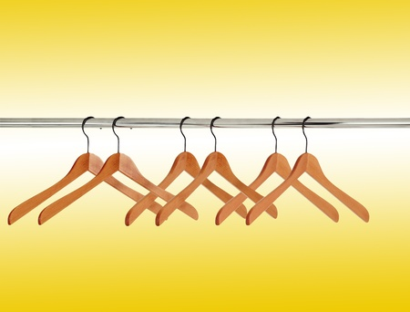 clothing rack: wooden clothes hangers over yellow background  Stock Photo