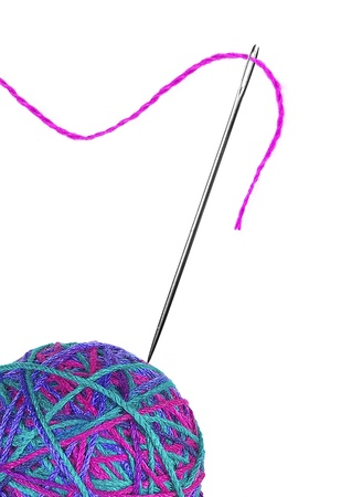 Colorful thread ball and needle with pink thread isolated on white photo