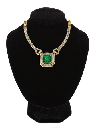 beautiful gold jewellery necklace with green stone on black mannequin isolated on white  photo
