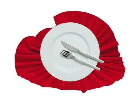 Fork, knife and white plate on a red cloth isolated on white photo