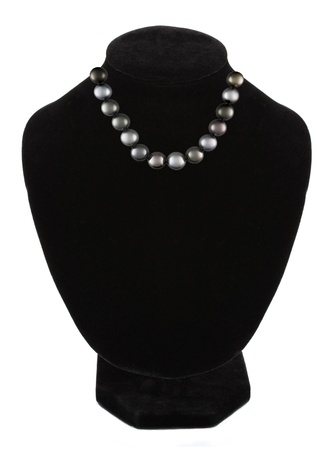 Black pearl necklace on black mannequin isolated on white background  photo