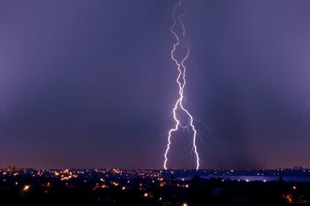 Lightning strike over dark blue sky in night city photo