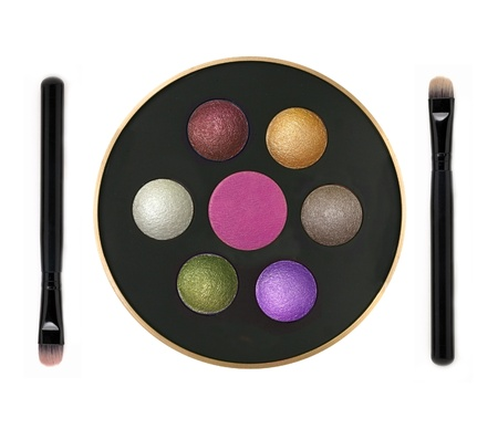 Multicolor eyeshadows in round box and brushes isolated on white photo