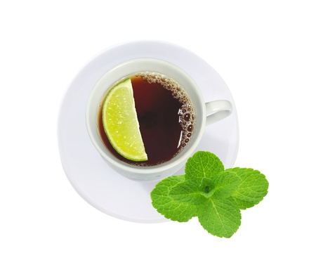 cup of tea with mint leaves and lime slice isolated on white photo