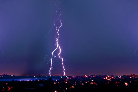 Lightning strike over dark blue sky in night city photo