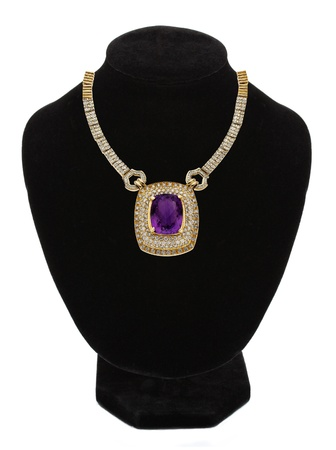 beautiful gold jewellery necklace with violet stone on black mannequin isolated on white  photo