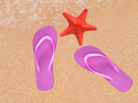 Pair of flip- flops on the sand with starfish photo