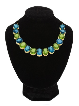 Pendant with green and blue gem stones on black mannequin isolated on white  photo