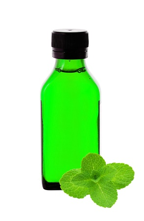 Close up of medicine bottle with green syrup and mint herb isolated on white background photo