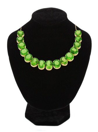 Pendant with green gem stones on black mannequin isolated on white  photo