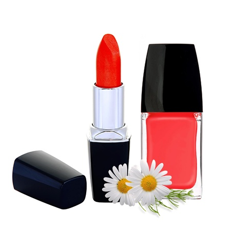 red nail polish, lipstick and chamomile flowers isolated on white background photo