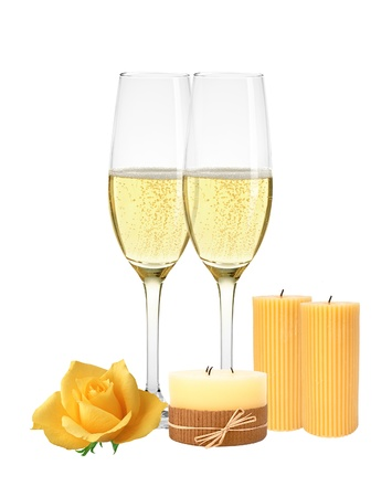 Two glasses of champagne, candles and yellow rose isolated on white background photo