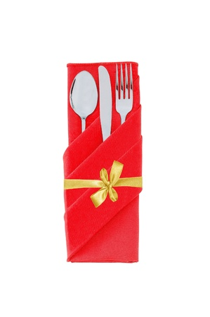 Fork, spoon and knife in red cloth with golden bow isolated on white background photo