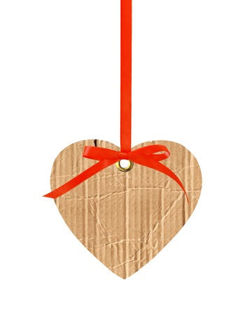 cardboard heart with red ribbon bow isolated on white photo