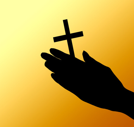 female hands with crucifix over brown  photo
