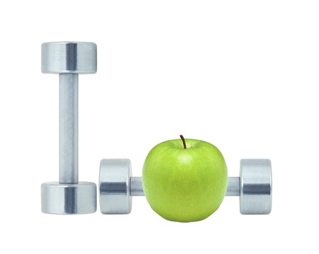 Chromed fitness dumbbells and green apple isolated on white background photo