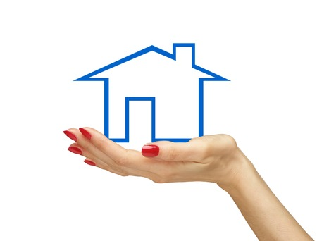 Blue house in woman hand isolated on white background. Real estate photo