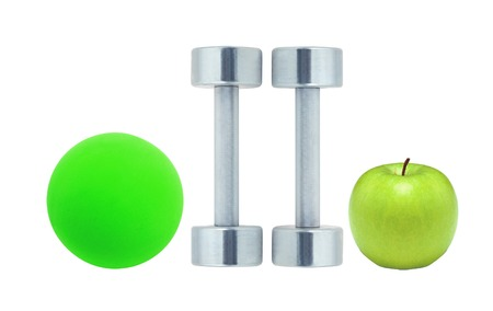Chromed fitness dumbbells, ball and green apple isolated on white background photo