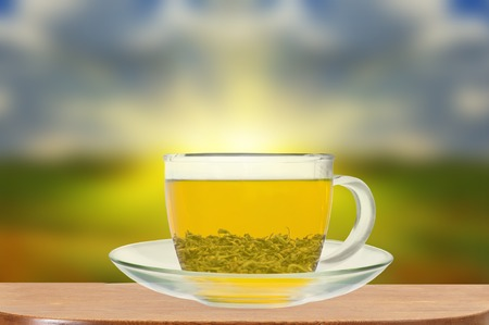 Transparent cup of green tea on wooden table close up photo