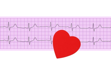 Textile heart over electrocardiogram graph on white background photo
