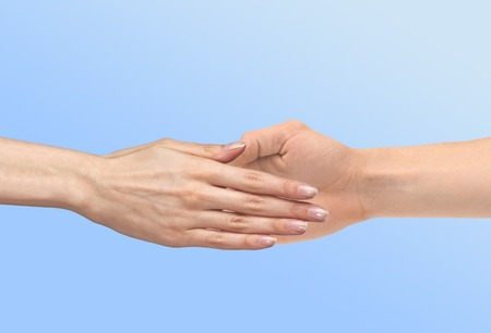 women's hand: Womens hand goes to the mans hand on blue background Stock Photo