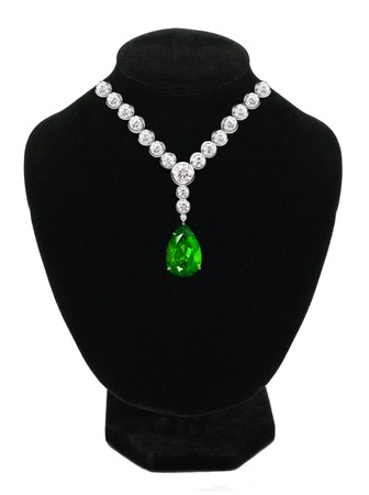 Diamond and emerald necklace on black mannequin isolated on white background photo
