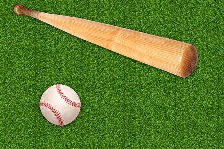 baseball ball and bat on green grass background photo