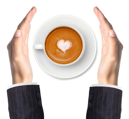 Latte coffee with heart symbol and woman hands isolated on white background photo