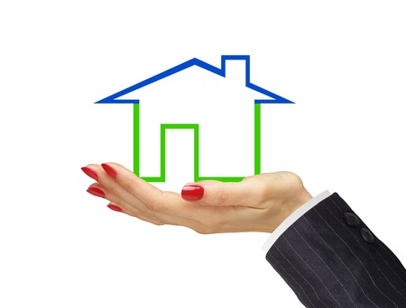 Green house in woman hand isolated on white background. Real estate photo