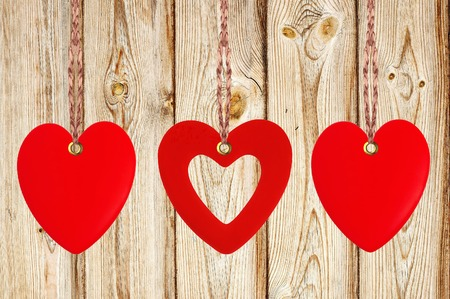 Three red hearts on the wooden weathered rustic background photo