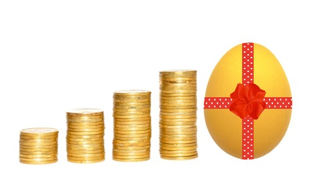 columns of gold coins and easter egg with red ribbon over white background photo
