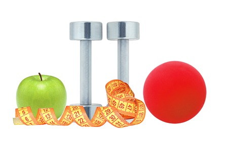 Chromed fitness dumbbells, measure tape red ball and green apple isolated on white background photo