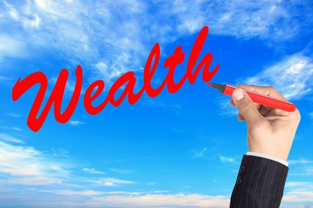 Hand writing word Wealth over blue sky background photo