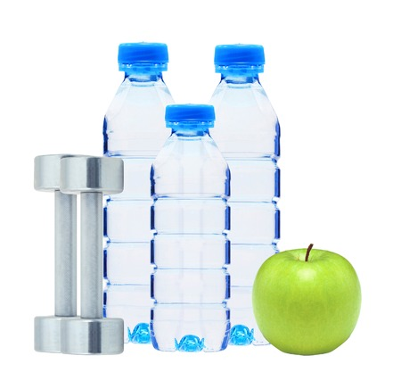 Blue bottles with water, chromed fitness dumbbells and green apple isolated on white background photo