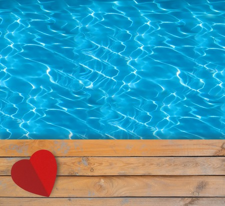 Swimming pool with blue clear water, wooden deck and red paper heart photo
