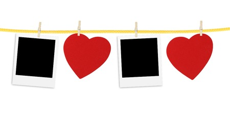 Vintage photos frame on the clothesline with hearts over white photo