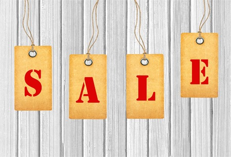 Sale tags over white wooden background photo