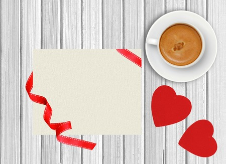 White cup of coffee and greeting card on wooden background photo