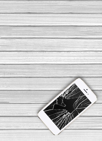 crashed: Modern mobile phone with broken screen on white wooden background