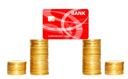 plastik: columns of gold coins and red credit card isolated on white background